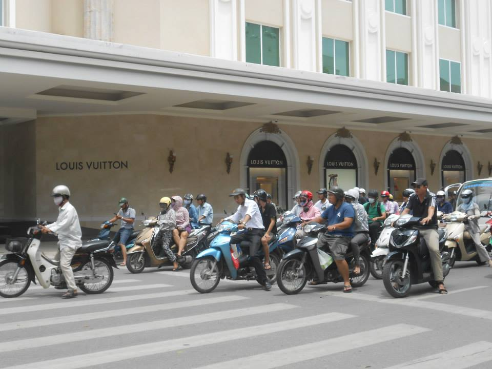 Scores of mopeds zip across the streets of Hanoi