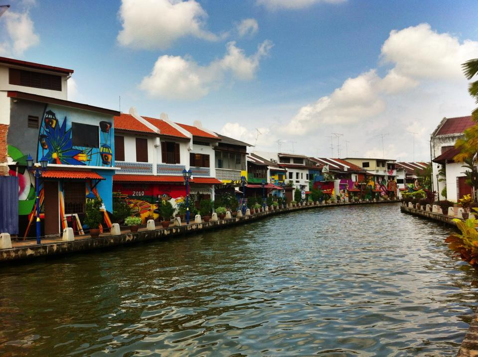 Graffiti marked houses line the riverside in Melacca